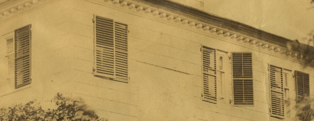 Detail of a photograph of the Morris-Jumel Mansion showing several windows with venetian blinds.